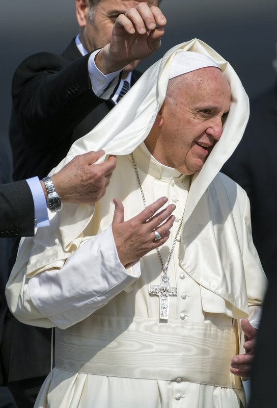 FILE - In this Feb. 12, 2016 file photo, wind blows part of Pope Francis' dress over his head as he arrives to Jose Marti Airport in Havana, Cuba. (AP Photo/Desmond Boylan, File)