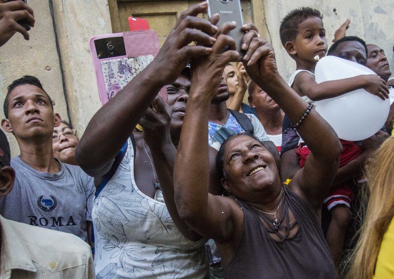 FILE - In this Sept. 8, 2018 file photo, people take pictures of the statue of the Virgin of Charity during an annual religious procession in Havana, Cuba. (AP Photo/Desmond Boylan, File)