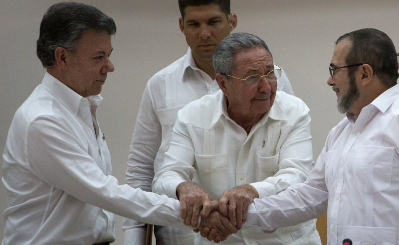 FILE - In this Sept. 23, 2015 file photo, Cuba's President Raul Castro brings together the hands of Colombian President Juan Manuel Santos, left, and Commander the Revolutionary Armed Forces of Colombia FARC) Timoleon Jimenez during a ceremony in Havana, Cuba, after Santos and the FARC overcame the last significant obstacle to a peace deal. (AP Photo/Desmond Boylan, File)