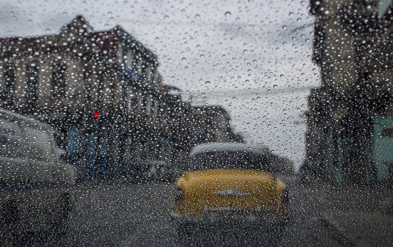 FILE - In this May 24, 2018 file photo, rain drops accumulate on a car's windshield as commuters wait at a red light in Havana, Cuba. (AP Photo/Desmond Boylan, File)