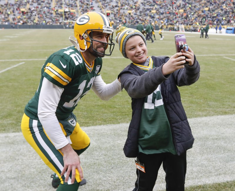 CORRECTS TO REMOVE SCORE- Simon McPhail takes a selfie with Green Bay Packers' Aaron Rodgers before an NFL football game against the Detroit Lions Sunday, Dec. (AP Photo/Mike Roemer)
