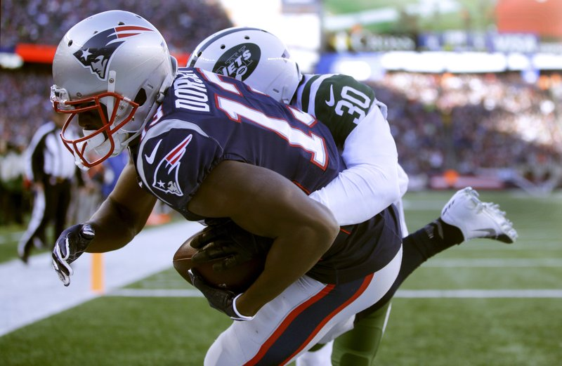 New England Patriots wide receiver Phillip Dorsett, left, catches a touchdown pass as New York Jets cornerback Rashard Robinson wraps him up in the end zone during the first half of an NFL football game, Sunday, Dec. (AP Photo/Steven Senne)