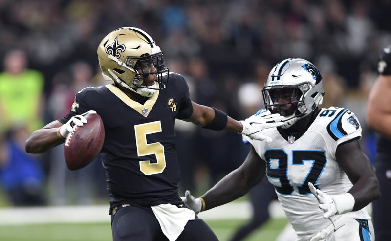 New Orleans Saints quarterback Teddy Bridgewater (5) drops back to pass under pressure from Carolina Panthers defensive end Mario Addison (97) in the first half of an NFL football game in New Orleans, Sunday, Dec. (AP Photo/Bill Feig)