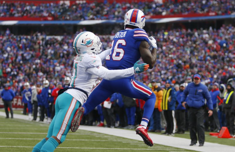 Buffalo Bills wide receiver Robert Foster (16) catches a 5-yard touchdown pass under pressure from Miami Dolphins defensive back Cornell Armstrong (31) during the second half of an NFL football game, Sunday, Dec. (AP Photo/Jeffrey T. Barnes)