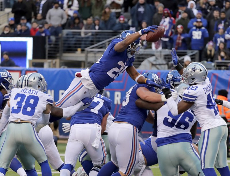 New York Giants' Saquon Barkley, top, scores a touchdown just before the ball is knocked from his hands during the second half of an NFL football game against the Dallas Cowboys, Sunday, Dec. (AP Photo/Frank Franklin II)