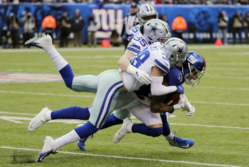 New York Giants' Evan Engram, right, is tacked by Dallas Cowboys defenders during the first half of an NFL football game, Sunday, Dec. (AP Photo/Frank Franklin II)