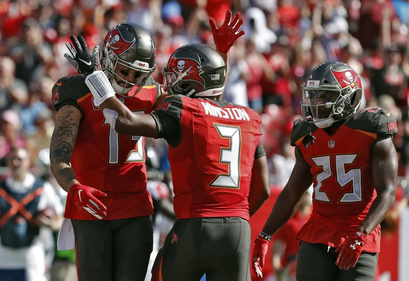 Tampa Bay Buccaneers wide receiver Mike Evans (13) celebrates with quarterback Jameis Winston (3) and running back Peyton Barber (25) after scoring against the Atlanta Falcons during the first half of an NFL football game Sunday, Dec. (AP Photo/Mark LoMoglio)