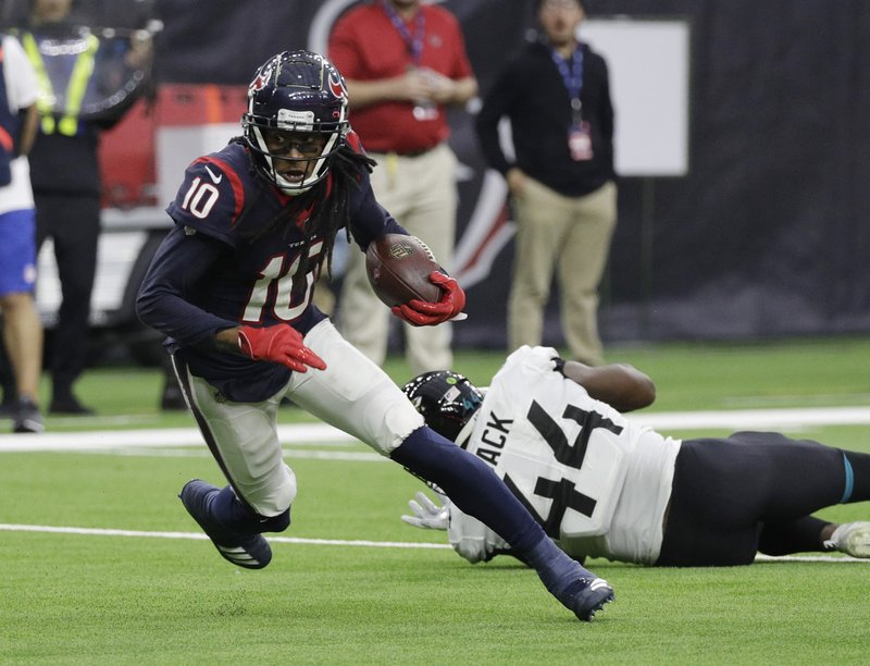 Houston Texans wide receiver DeAndre Hopkins (10) runs past Jacksonville Jaguars middle linebacker Myles Jack (44) after making a catch during the first half of an NFL football game, Sunday, Dec. (AP Photo/David J. Phillip)