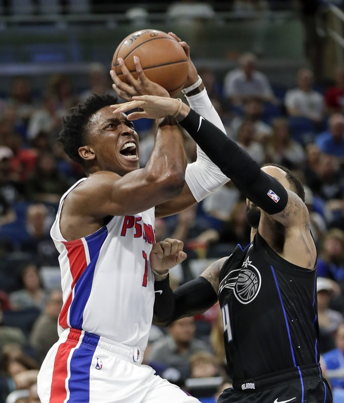 Detroit Pistons' Stanley Johnson, left, shoots against Orlando Magic's D.J. Augustin, right, during the first half of an NBA basketball game, Sunday, Dec. (AP Photo/John Raoux)