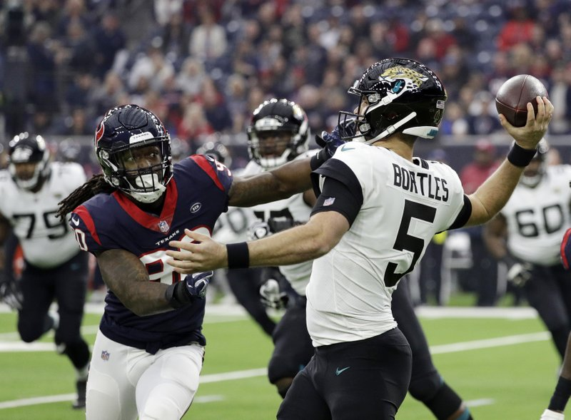 Jacksonville Jaguars quarterback Blake Bortles (5) is pressured by Houston Texans outside linebacker Jadeveon Clowney (90) during the first half of an NFL football game, Sunday, Dec. (AP Photo/David J. Phillip)