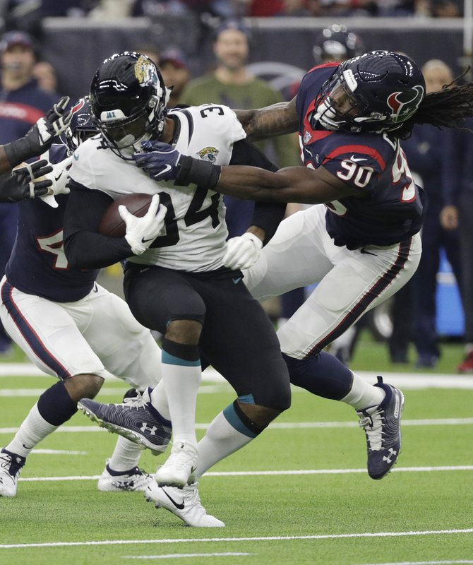 Jacksonville Jaguars running back Carlos Hyde (34) is stopped by Houston Texans outside linebacker Jadeveon Clowney (90) during the first half of an NFL football game, Sunday, Dec. (AP Photo/David J. Phillip)