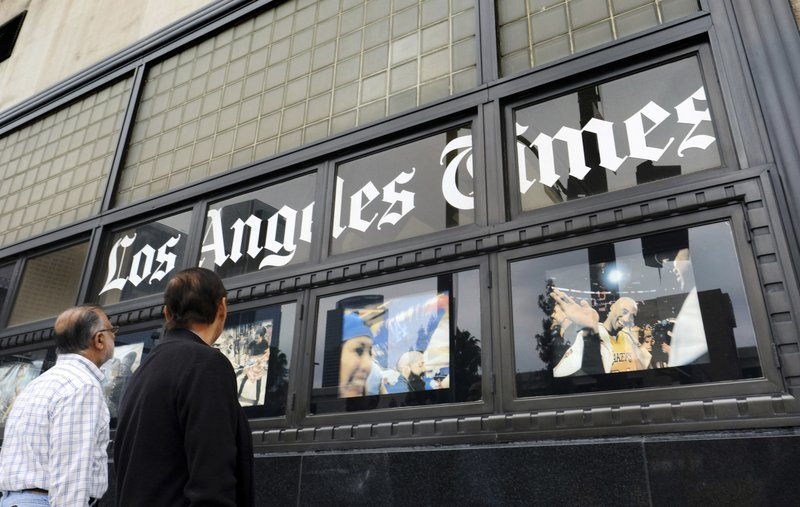 FILE - In this May 16, 2016, file photo, pedestrians look at news photos posted outside the Los Angeles Times building in downtown Los Angeles. (AP Photo/Richard Vogel, File)
