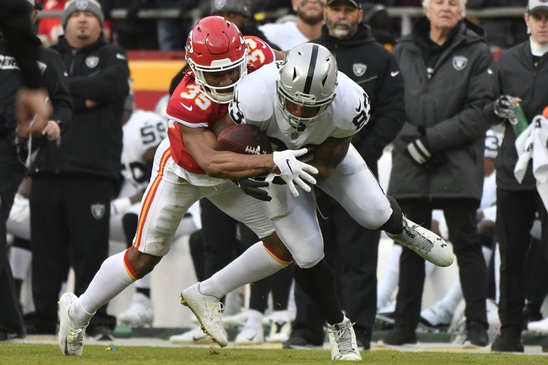 Oakland Raiders tight end Darren Waller (83) makes a catch against Kansas City Chiefs cornerback Charvarius Ward (35) during the first half of an NFL football game in Kansas City, Mo. (AP Photo/Ed Zurga)