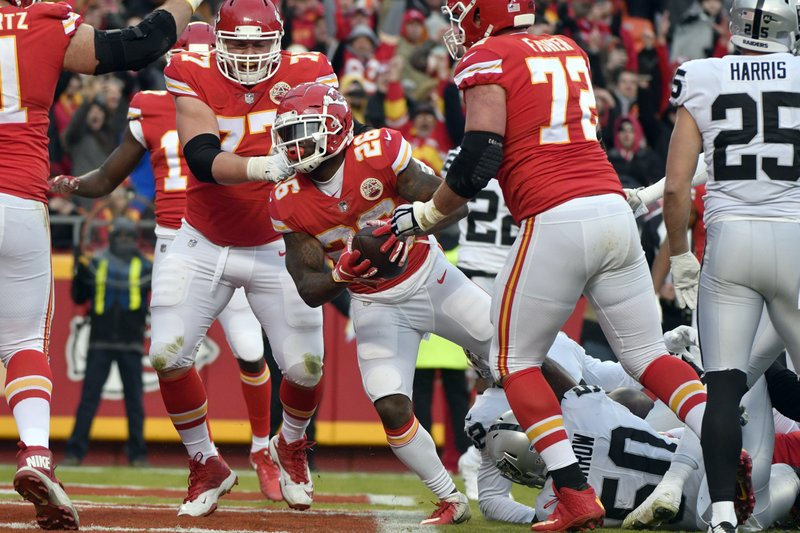 Kansas City Chiefs running back Damien Williams (26) scores a touchdown between offensive guard Andrew Wylie (77) and offensive tackle Eric Fisher (72) and past Oakland Raiders linebacker Nicholas Morrow (50) during the first half of an NFL football game in Kansas City, Mo. (AP Photo/Ed Zurga)