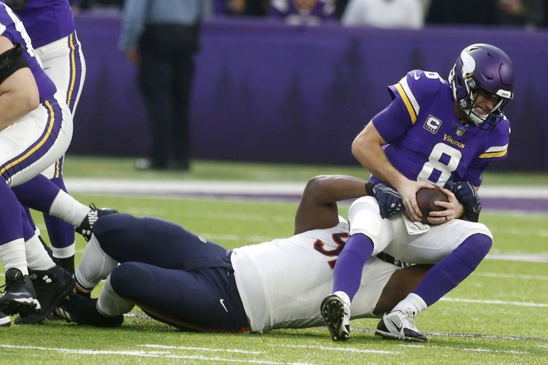 Minnesota Vikings quarterback Kirk Cousins (8) is sacked by Chicago Bears nose tackle Eddie Goldman during the first half of an NFL football game, Sunday, Dec. (AP Photo/Jim Mone)