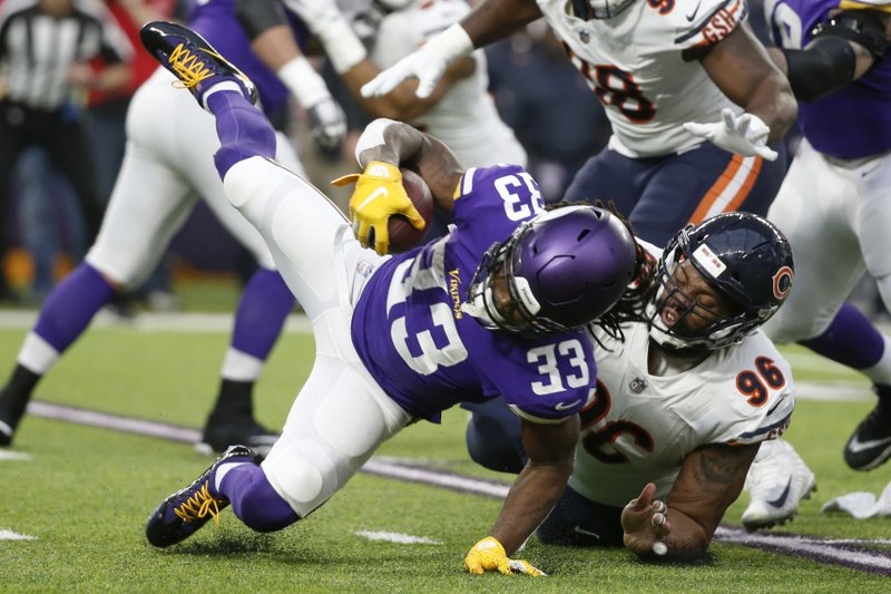 Minnesota Vikings running back Dalvin Cook (33) is tackled by Chicago Bears defensive end Akiem Hicks (96) during the first half of an NFL football game, Sunday, Dec. (AP Photo/Bruce Kluckhohn)