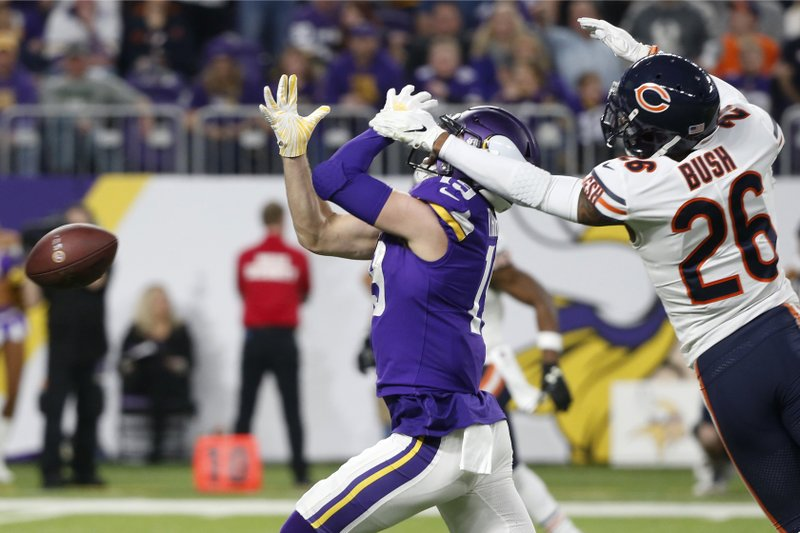 Chicago Bears defensive back Deon Bush (26) grabs the face mask of Minnesota Vikings wide receiver Adam Thielen during the first half of an NFL football game, Sunday, Dec. (AP Photo/Bruce Kluckhohn)