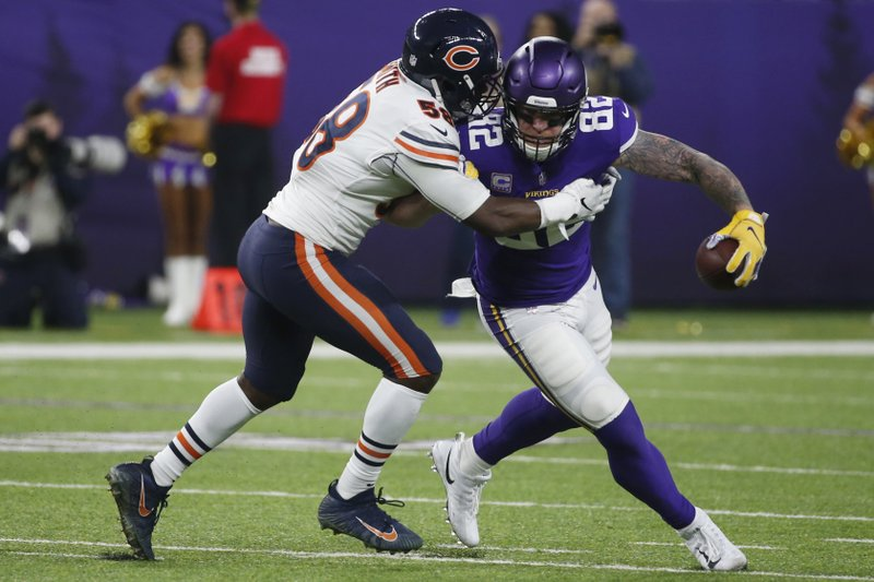 Minnesota Vikings tight end Kyle Rudolph (82) is tackled by Chicago Bears inside linebacker Roquan Smith, left, after catching a pass during the first half of an NFL football game, Sunday, Dec. (AP Photo/Bruce Kluckhohn)