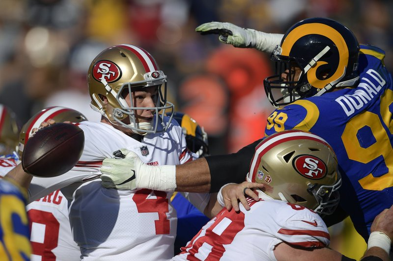 Los Angeles Rams defensive end Aaron Donald, right, puts pressure on San Francisco 49ers quarterback Nick Mullens during the first half in an NFL football game Sunday, Dec. (AP Photo/Mark J. Terrill)