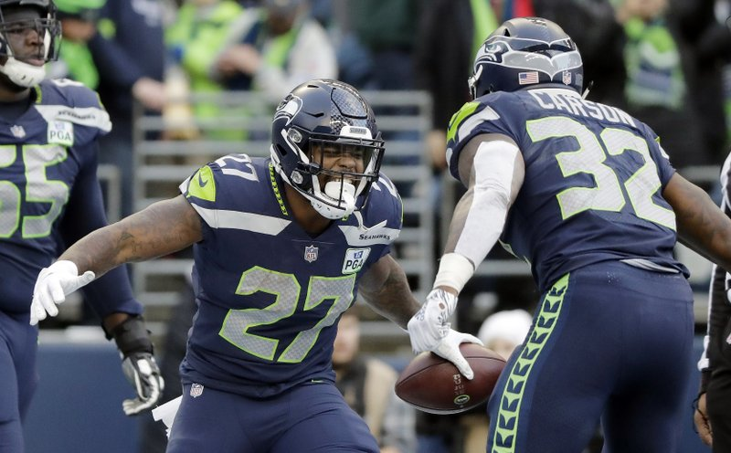 Seattle Seahawks' Mike Davis (27) celebrates his touchdown with Chris Carson during the second half of an NFL football game against the Arizona Cardinals, Sunday, Dec. (AP Photo/Ted S. Warren)