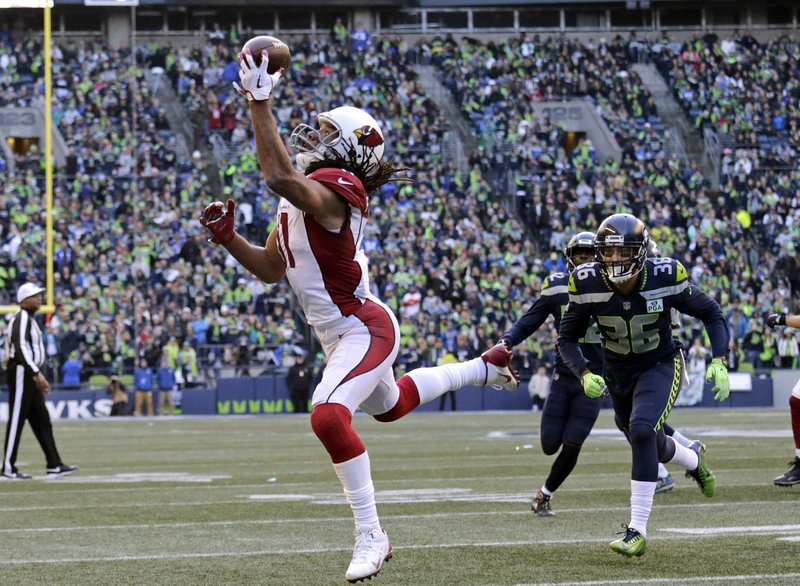 Arizona Cardinals' Larry Fitzgerald, left, snags a one-handed touchdown pass against the Seattle Seahawks during the first half of an NFL football game, Sunday, Dec. (AP Photo/John Froschauer)