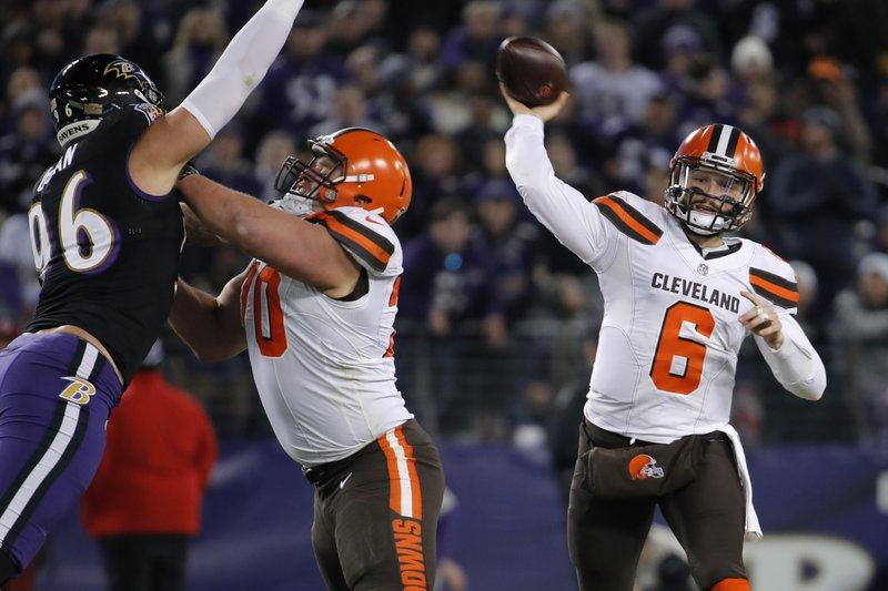 Cleveland Browns quarterback Baker Mayfield, right, throws a pass in the first half of an NFL football gameagainst the Baltimore Ravens, Sunday, Dec. (AP Photo/Carolyn Kaster)