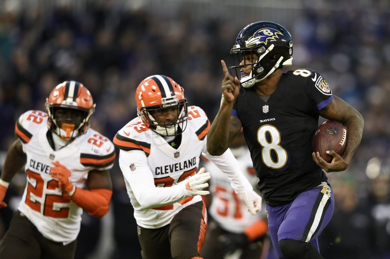 Baltimore Ravens quarterback Lamar Jackson, right, rushes for a touchdown past Cleveland Browns free safety Jabrill Peppers, back left, and strong safety Damarious Randall in the first half of an NFL football game, Sunday, Dec. (AP Photo/Gail Burton)
