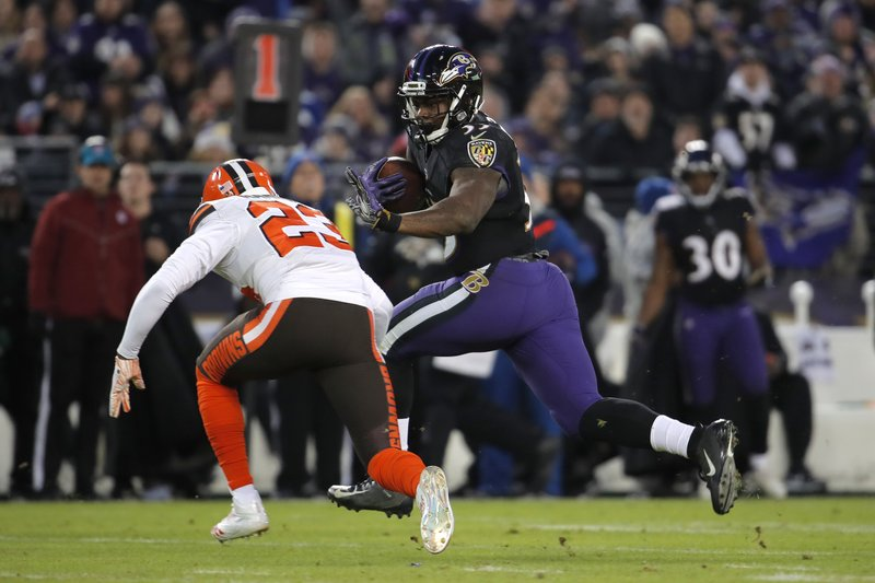 Baltimore Ravens running back Gus Edwards, right, rushes past Cleveland Browns strong safety Damarious Randall in the first half of an NFL football game, Sunday, Dec. (AP Photo/Carolyn Kaster)