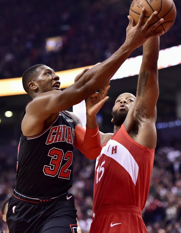 Chicago Bulls guard Kris Dunn (32) shoots as Toronto Raptors center Greg Monroe (15) defends during first-half NBA basketball game action in Toronto, Ontario, Sunday, Dec. (Frank Gunn/The Canadian Press via AP)