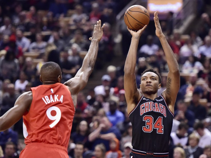 Chicago Bulls forward Wendell Carter Jr. (34) shoots over Toronto Raptors forward Serge Ibaka (9) during first-half NBA basketball game action in Toronto, Ontario, Sunday, Dec. (Frank Gunn/The Canadian Press via AP)