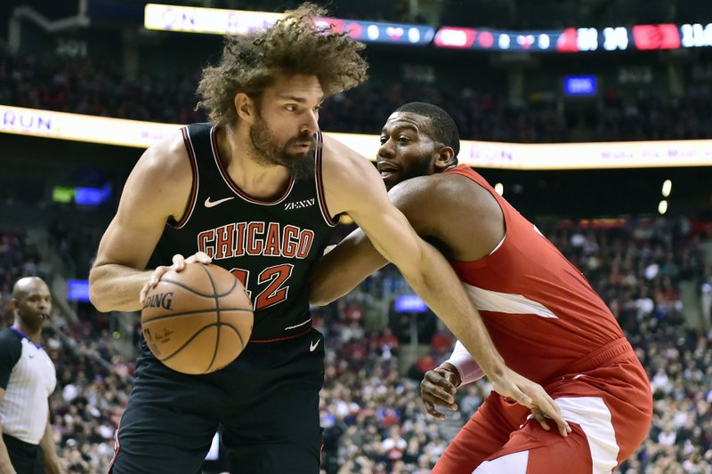 Chicago Bulls center Robin Lopez (42) drives to the net against Toronto Raptors center Greg Monroe (15) during the first half of an NBA basketball game, Sunday, Dec. (Frank Gunn/The Canadian Press via AP)