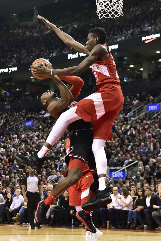 Toronto Raptors forward Chris Boucher (25) fouls Chicago Bulls guard Kris Dunn (32) driving to the net during the first half of an NBA basketball game, Sunday, Dec. (Frank Gunn/The Canadian Press via AP)