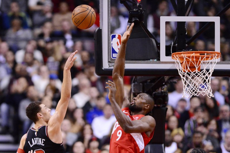 Toronto Raptors forward Serge Ibaka (9) blocks a shot from Chicago Bulls guard Zach LaVine (8) during second-half NBA basketball game action in Toronto, Ontario, Sunday, Dec. (Frank Gunn/The Canadian Press via AP)