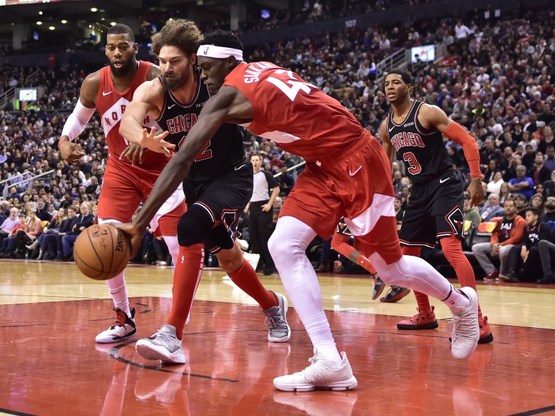 Toronto Raptors forward Pascal Siakam (43) collects a rebound in front of Chicago Bulls center Robin Lopez (42) during second-half NBA basketball game action in Toronto, Ontario, Sunday, Dec. (Frank Gunn/The Canadian Press via AP)