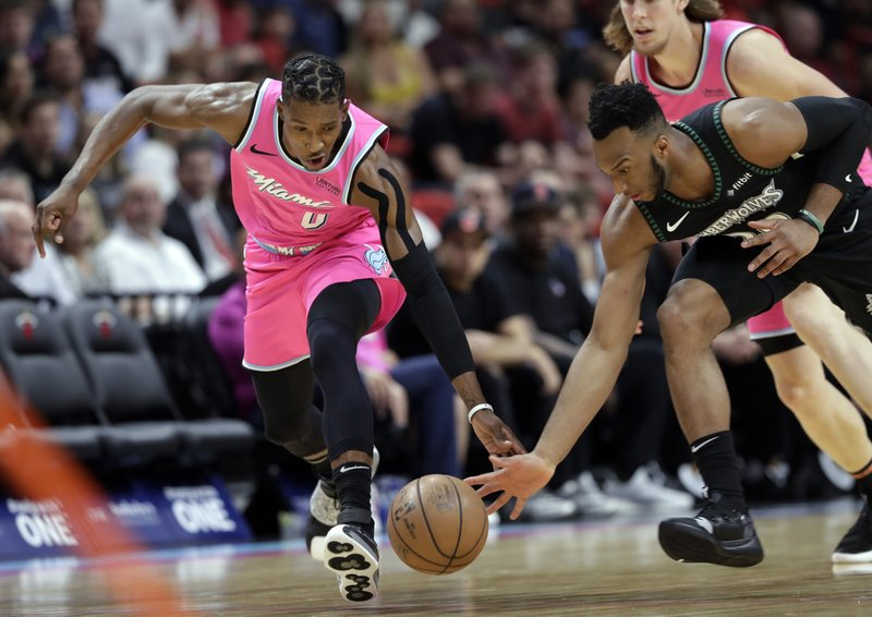 Miami Heat guard Josh Richardson (0) and Minnesota Timberwolves guard Josh Okogie go for a loose ball during the first half of an NBA basketball game, Sunday, Dec. (AP Photo/Lynne Sladky)