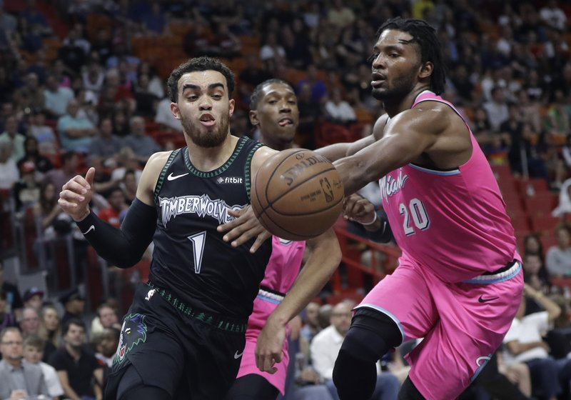 Miami Heat forward Justise Winslow (20) defends Minnesota Timberwolves guard Tyus Jones (1) during the first half of an NBA basketball game, Sunday, Dec. (AP Photo/Lynne Sladky)