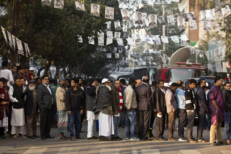 Bangladeshis line up to cast their votes outside a polling station in Dhaka, Bangladesh, Sunday, Dec. (AP Photo/Anupam Nath)