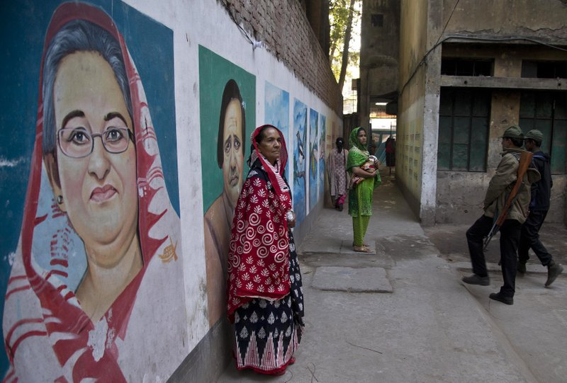 Bangladeshi women stand next to a mural displaying portraits of Bangladesh Prime Minister Sheikh Hasina, left, and others after casting their votes at a polling station in Dhaka, Bangladesh, Sunday, Dec. (AP Photo/Anupam Nath)