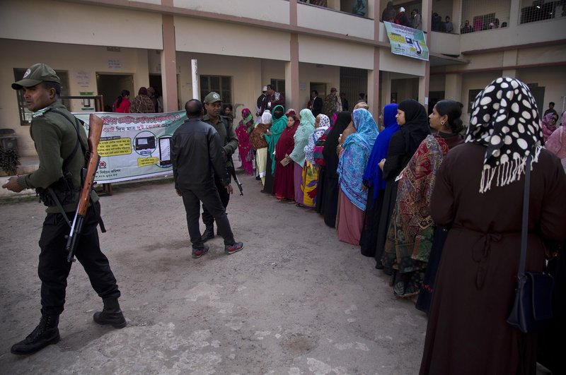 Bangladeshi security personnel stand guard as women line up to cast their votes outside a polling station in Dhaka, Bangladesh, Sunday, Dec. (AP Photo/Anupam Nath)