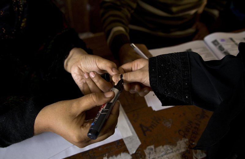 A Bangladeshi polling officer puts indelible ink on the finger of a voter at a polling station in Dhaka, Bangladesh, Sunday, Dec. (AP Photo/Anupam Nath)