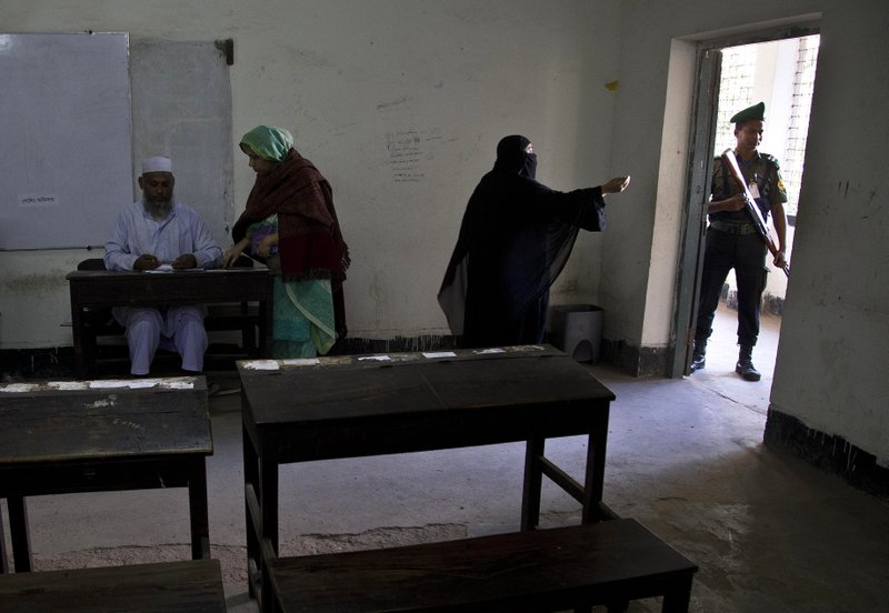 A Bangladeshi Muslim woman asks for some help before casting her vote at a polling station in Dhaka, Bangladesh, Sunday, Dec. (AP Photo/Anupam Nath)