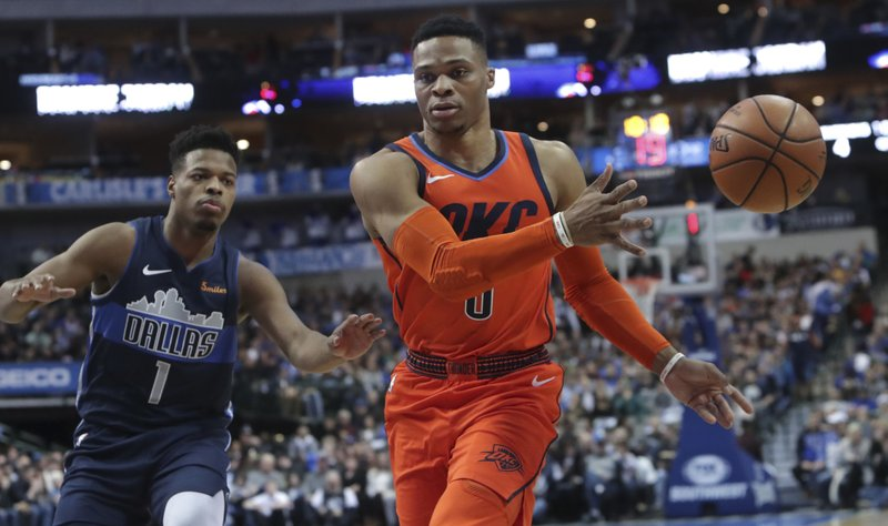 Oklahoma City Thunder guard Russell Westbrook (0) passes the ball in front of Dallas Mavericks guard Dennis Smith Jr. (1) during the first half of an NBA basketball game in Dallas, Sunday, Dec. 30, 2018. (AP Photo/LM Otero)