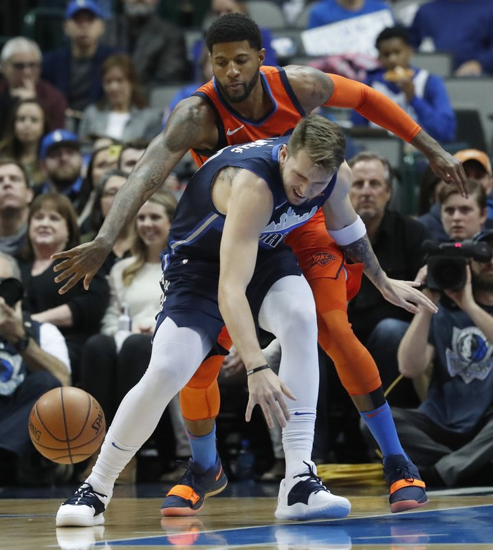 Oklahoma City Thunder forward Paul George, top, reaches to disrupt the dribble by Dallas Mavericks forward Luka Doncic, of Germany, during the first half of an NBA basketball game in Dallas, Sunday, Dec. (AP Photo/LM Otero)