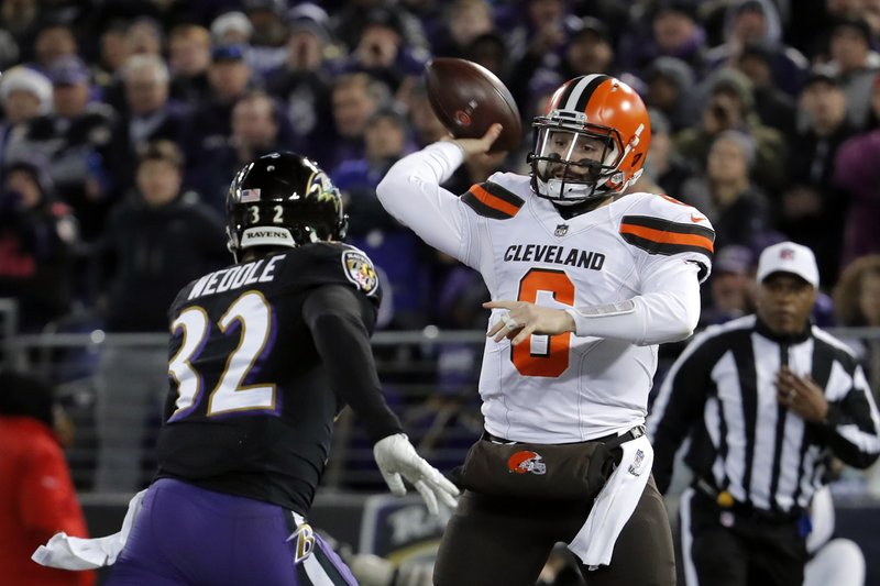 Cleveland Browns quarterback Baker Mayfield, right, throws a pass as he is pressured by Baltimore Ravens free safety Eric Weddle in the first half of an NFL football game, Sunday, Dec. (AP Photo/Carolyn Kaster)