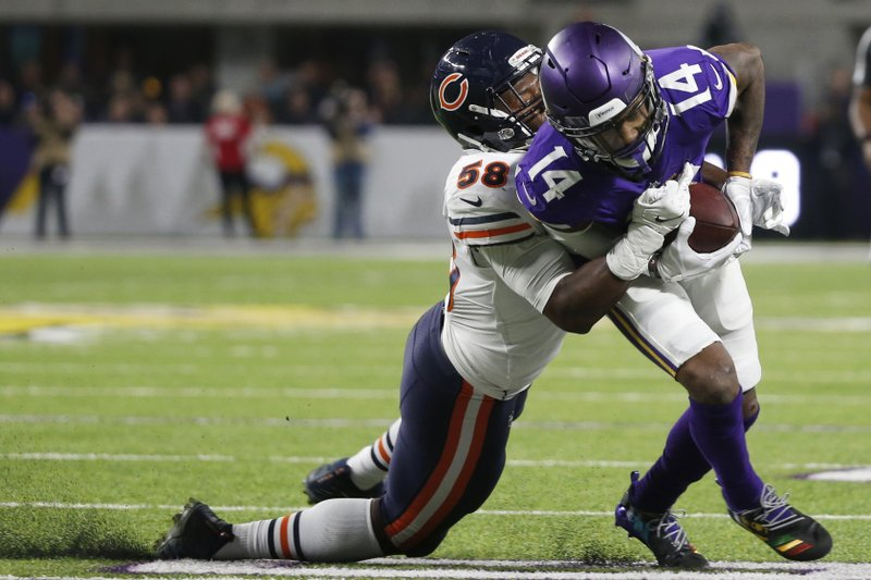 Minnesota Vikings wide receiver Stefon Diggs (14) tries to break a tackle by Chicago Bears inside linebacker Roquan Smith, left, during the second half of an NFL football game, Sunday, Dec. (AP Photo/Bruce Kluckhohn)