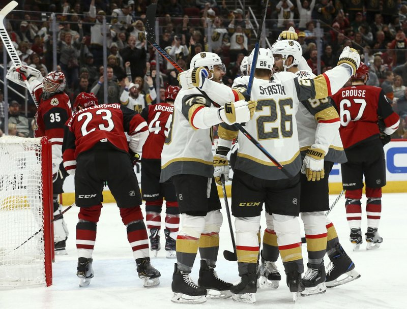 Vegas Golden Knights center Paul Stastny (26) celebrates his goal against the Arizona Coyotes with left wing Valentin Zykov (73) and right wing Alex Tuch (89) as Coyotes goaltender Darcy Kuemper (35) and Coyotes defenseman Oliver Ekman-Larsson (23) look for the puck during the first period of an NHL hockey game Sunday, Dec. (AP Photo/Ross D. Franklin)