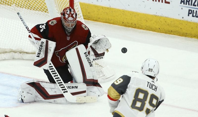 Arizona Coyotes goaltender Darcy Kuemper (35) makes a save on a shot by Vegas Golden Knights right wing Alex Tuch (89) during the second period of an NHL hockey game Sunday, Dec. (AP Photo/Ross D. Franklin)