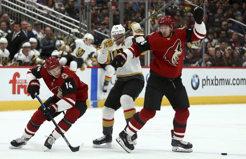 Arizona Coyotes right wing Richard Panik (14) skates around Vegas Golden Knights right wing Reilly Smith (19) and Coyotes defenseman Ilya Lyubushkin, right, to get to the puck during the first period of an NHL hockey game Sunday, Dec. (AP Photo/Ross D. Franklin)