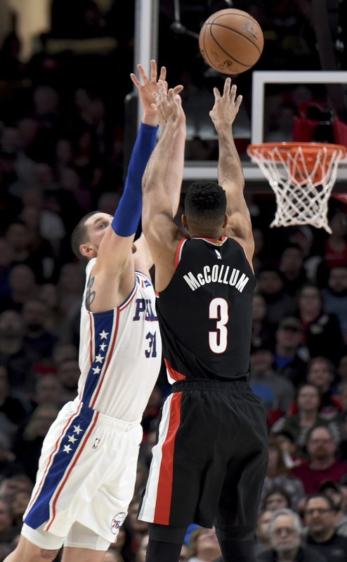 Portland Trail Blazers guard CJ McCollum, right, hits a shot over Philadelphia 76ers forward Mike Muscala, left, during the first half of an NBA basketball game in Portland, Ore. (AP Photo/Steve Dykes)