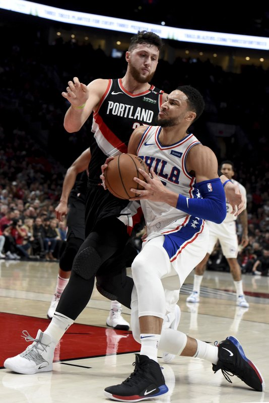 Philadelphia 76ers guard Ben Simmons, right, drives to the basket on Portland Trail Blazers center Jusuf Nurkic, left, during the first half of an NBA basketball game in Portland, Ore. (AP Photo/Steve Dykes)